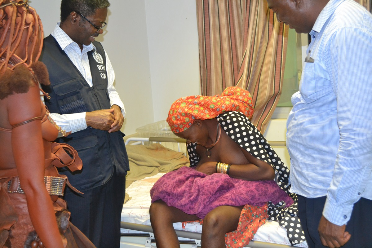 Teenage girl breastfeeding her newborn baby while WHO Representative, Dr  Charles Sagoe-Moses and Mr Thomas Shapumbu, Kunene Regional Health Director looks on