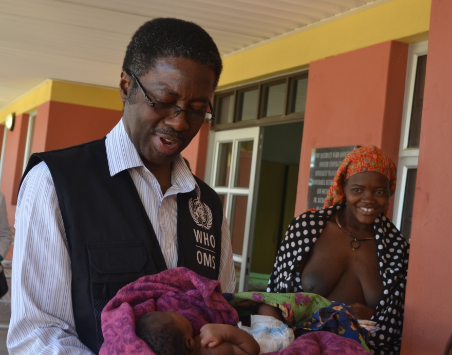 Dr Sagoe-Moses holding the newborn as the mother looks on
