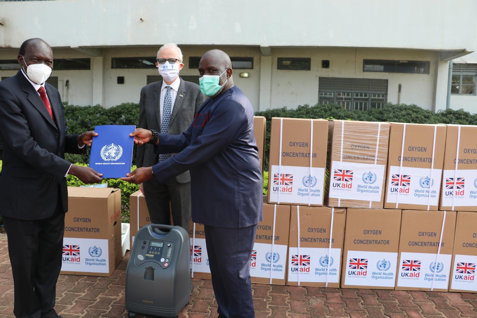 Dr Olushayo Olu, WHO Representative handing over the donation certificate to Dr Mayen Machut Achiek, Undersecretary, Ministry of Health in the presence of Chris Trott, British Ambassador