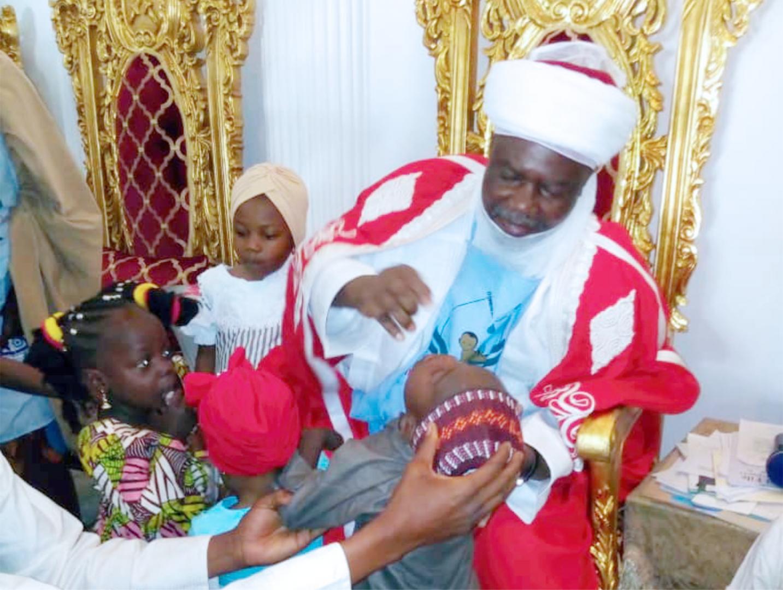 Emir of Argungu vaccinating a child