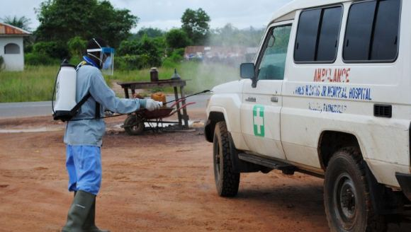 A_health_worker_sprays_disinfectant_on_an_ambulance_in_Nedowein_Liberia_in_July_2015.JPG