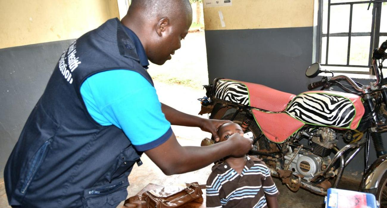 WHO Staff Dr. Tenywa immunizes a child at Namutumba Health Center III