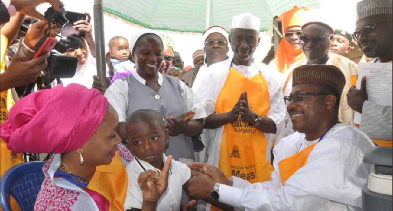 ED NPHCDA Dr Faisal Shuaib vaccinating the child of the Governor of Kaduna state while the Governor's wife Hajiya Ummi El Rufai looks on.