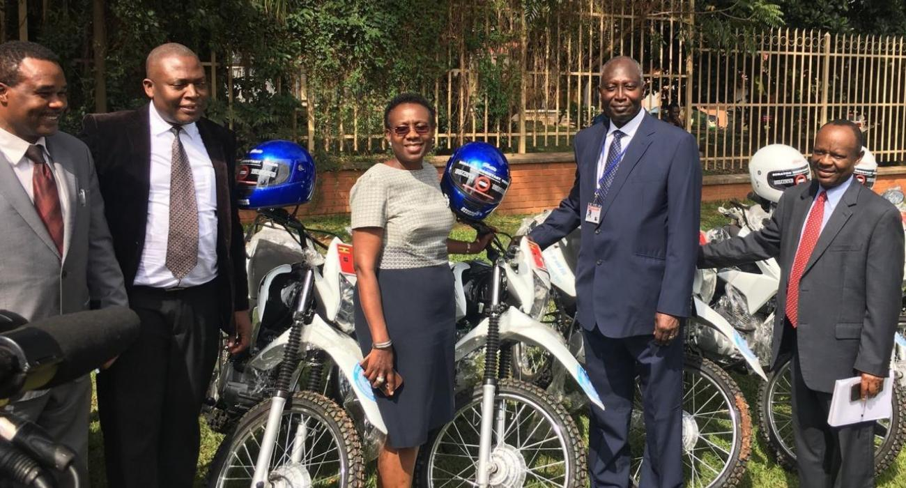 Minister of Health, Dr, Jane Ruth Aceng receives the motorcycles from WHO Acting Rep in Uganda, Dr. Jack Abdoulie as Ministry officials look on