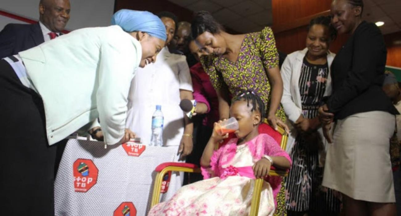 Minister for Health, Hon. Ummy Mwalimu, witnessing a child taking the new child-friendly TB medicine