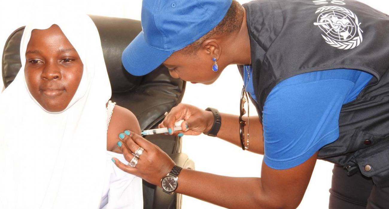 WHO staff vaccinating a girl during the occasion.