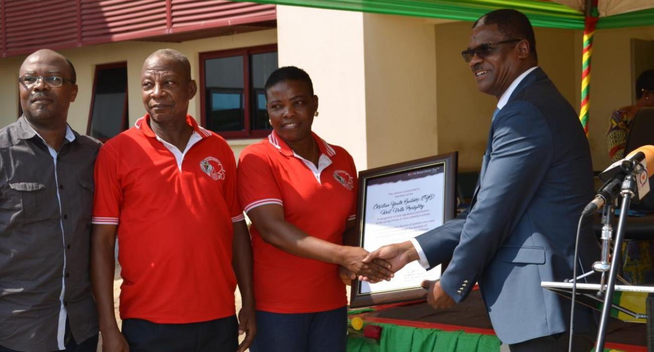 Dr Kaluwa presenting a citation to one of the blood donation organizations