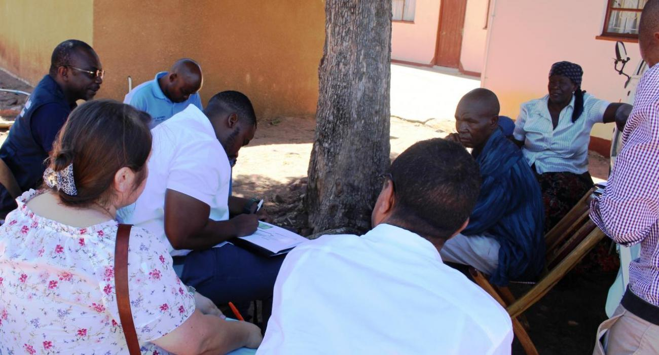 Participants interviewing a community member who once suffered from malaria