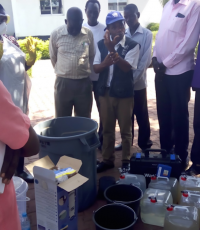 Alex Sokemawu WHO WASH and Logistics technical lead demonstrating water quality control testing
