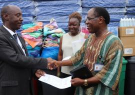 Dr Alex Gasasira handing over a consignment of assorted items for E.S Grant Hospital to Dr Francis Kateh, Deputy Minister of Health/CMO. Looking on is Mrs. Cooper, the Hospital administrator