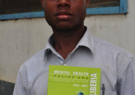 A mental health worker displaying a copy of the Mental Health Policy and Strategic Plan