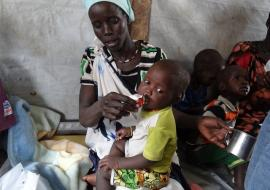 Woman giving PlumpyNut nutritional aid to her children in former Unity State