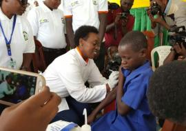 The Minister of Health, Dr Diane Gashumba vaccinating a pupil on HPV
