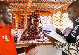 Liberia: Mr Tamba Alpha, surveillance officer, is inspecting isolation rooms at a Voinjama checkpoint with Mr Charles Ntege, WHO county coordinator. WHO/M. Winkler