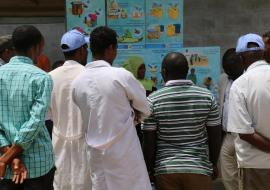 A WHO/UNICEF Risk Communication team member explains AWD prevention and control to health workers and residents of Gabo Gabo Kabele using pictorial posters (Photo: Ms Tseday Zerayaco)