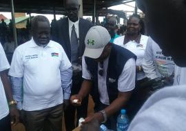 Dr Riek Gai Kok, the Honorable Minister of Health is ready to take Ivermectin tablets administered by WHO NTD Program manager at the Freedom Square Ground in Tonj State. Photo WHO.