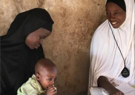 A community oriented resource person in Niger State examines a young child for pneumonia