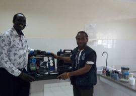 Mr Alex Freeman, handing over the water quality testing kit to the national public health laboratory technician in charge for water quality and safety testing.