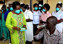 A TB patient receives treatment drugs from the Minister of Health on Sarah Opendi as other health workers look on