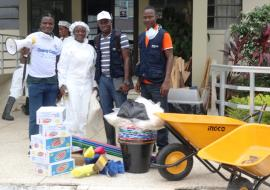 Mrs. Mama Koffa, Acting Deputy Director  JFK Medical Center, receives donation  of cleaning materials from WHO team