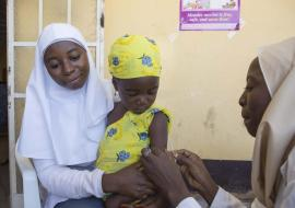 Health workers administering vaccine to an eligible child