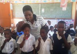 Children being assisted by a teacher to take Albendazole for STHs deworming