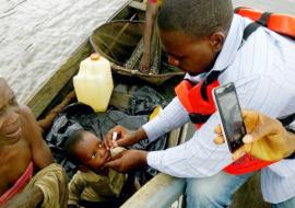 Vaccinator immunizing an eligible child in a boat with OPV during IPDS from his own boat