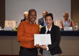 Mr Christopher Raboude, Nutritionist, Rodrigues Island, receiving the Certificate of Participation from Mrs Aryamah Doomun, Chief Nutritionist.  In the background, Dr I. Nawoor, Ag Director Health Services, Dr L. Musango, WHO Representative in Mauritius and Dr H. Bekele, Nutrition Advisor, WHO IST/ESA