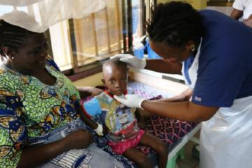 Photo of a nurse attending to Moses while Ebie looks on. The child's health has improved considerably due to the quality of care he received at the hospital