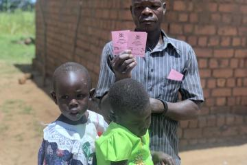Proud father shows off his daughter's immunization cards