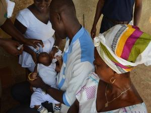 A proud father holding his baby whiles the infant receives Oral Polio Vaccine (OPV)
