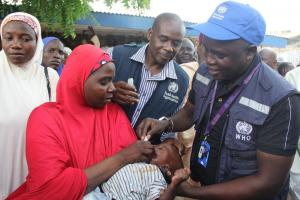 WHE Emergency Manager, Dr. Collins Owili vaccinates a child against cholera during the flagoff ceremong of the OCV campaign in Borno state. Credits: WHO CE.Onuekwe