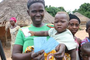 A woman and her child in Yendeya Village displaying her child's measles vaccination card. Photo credit: WHO/S. Gborie