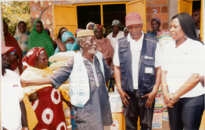 Centre (from left to right) : In light blue jacket, Baba Idris Haliru, Dr Andrew Mbewe (WHO) and Mrs Abigael Molme (Molme Foundation). Behind: Some of the beneficiaries of the intervention at Goza IDP camp.