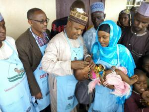 Alhaji Mohammed Abubakar (3rd left) Chairman of Tarmuwa LGA Yobe State immunizing a child during OBR flag off.