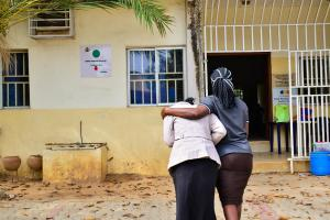 A patient supported by a relative into a health facility in Abuja