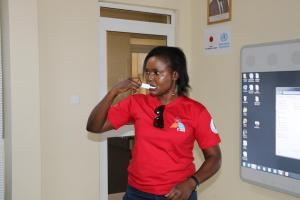 Ms Betty Araba of UNAIDS swabbing her mouth for an oral fluid sample for self-testing