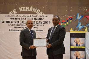 Dr Hon Anwar Husnoo, Minister of Health and Quality of Life receiving the 'Certificate of Appreciation' from Dr Laurent Musango, WHO Representative in Mauritius on behalf of Dr Tedros, Director General and Dr Moeti, Regional Director of the World Health Organization during the celebration of the World No-Tobacco Day 2019