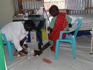 Health care worker dressing wound on a woman's leg in Bentiu
