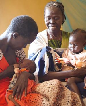 With Bakhita on her lap, Tereza encourages Ajonga to breastfeed her granddaughter, baby Akot.