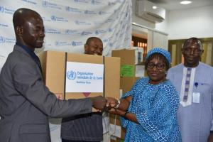Directeur de Cabinet du Ministère de Santé, Monsieur Emmanuel Sorgho, is receiving a kit from the Burkina Faso WR Dr. Alimata J. Diarra-Nama.