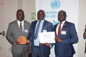 Honorable Minister of Health Jappie Mhango MP holding the UN Interagency Task Force award for NCD prevention and control