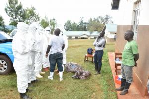 Ministry of Health and WHO staff teaching health workers proper donning and doffing of a Personal Protective Equipment