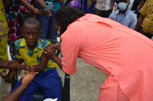 Health Minister, Dr. Jallah vaccinating first child during the TCV launch in Monrovia