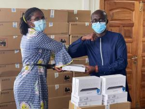 Dr Sally Ann Ohene DPC Officer presenting the tablets to Dr Kwame Amponsah-Achiano, EPI Manager, GHS