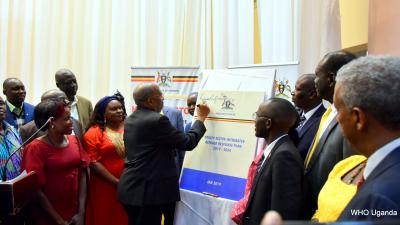 Prime Minister of Uganda Dr Ruhakana Ruganda signs on a dummy copy of the HSIRRP to launch the plan as government officials and partners look on
