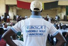 "Man wearing tshirt with text ""together we shall overcome Ebola"" at a social mobilization event in Guinea WHO /Cristiana Salvi"