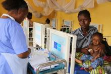 A nurse providing care to a sick child at the paediatric unit at the Kenema District Government Hospital.