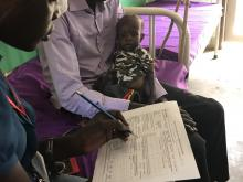 Medical doctor recording the daily management form to monitor the child's progress. Photo: WHO.