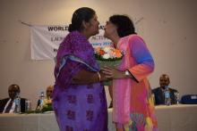 Dr (Mrs) M. Timol, Director General Health Services, receiving a bouquet from a lady